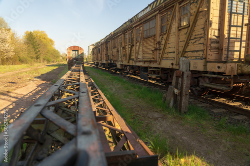 Obraz Verfallenes Bahnareal mit Wagons und Trägern - fototapety do salonu