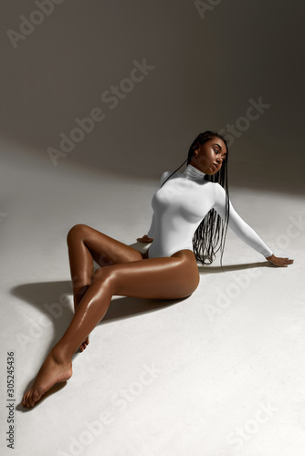 Fotografie, Obraz African woman portrait in white underwear on dark background