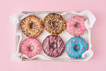 Different Types Of Colorful Donats Decorated Sprinkles And Icing In Box On A Pink Background, Top View
