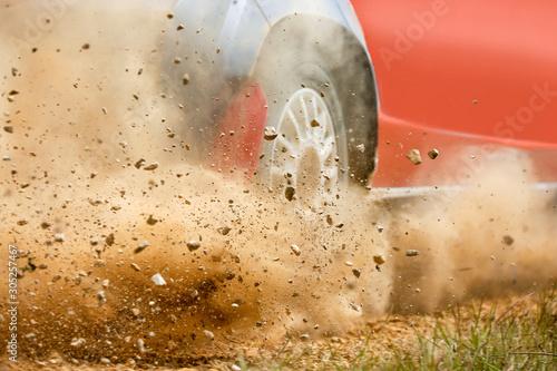 Fotomural  Gravel splashing from rally race car drift on track.
