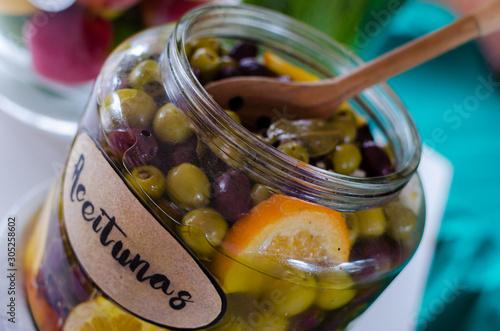 Photo Aceitunas maceradas con hierbas y cítricos en un envase de vidrio
