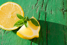 Yellow Juicy Lemon Slices With Mint Leaves  On Wooden Green Background With Hard Light, On Strong Sunlight With Long Dark Shadow, Contrast Photography, Mojito Ingredients