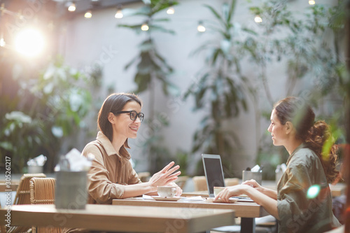 Side view portrait of two modern young women sitting at table in cafe and smiling cheerfully enjoying lunch together, copy space