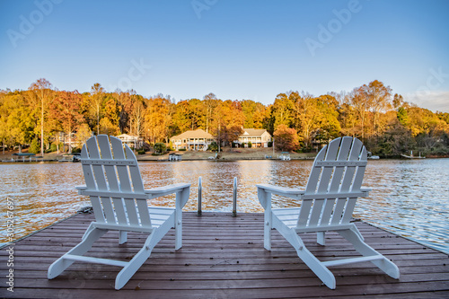 Adirondack style chairs on a dock, overlooking a beautiful, quiet, lake Fototapeta