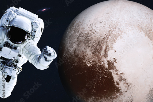 Платно Astronaut near Planet Pluto of Solar system in space with far galaxy on the background