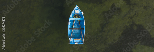Fotografie, Obraz Blue rowing boat top down aerial with ocean background