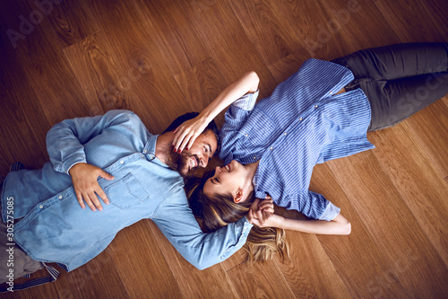 Cuadros en Lienzo Top view of attractive caucasian couple in love lying down on floor, cuddling and looking at each other