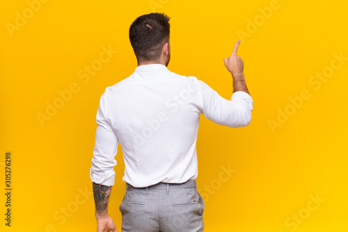 Valokuva  young handosme man standing and pointing to object on copy space, rear view agai