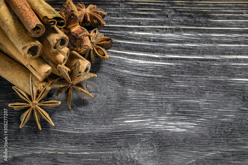 Photo copy space dried star anise flowers and cinnamon tubes on wooden background, top composition of seasoning and illustration