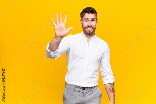 Fototapeta young handosme man smiling and looking friendly, showing number five or fifth wi