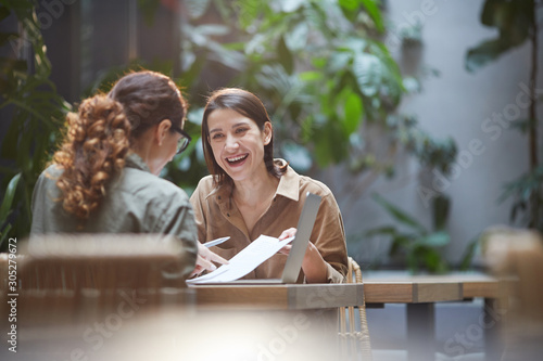 Obraz Portrait of cheerful young woman talking to friend or colleague during business meeting on outdoor cafe terrace, copy space - fototapety do salonu