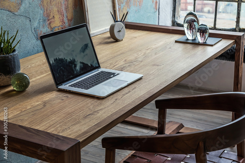 Obraz Stylish interior design of office space in loft apartment with wooden desk, chair, office supplies, laptop, plants and elegant accessories. Modern home office decor. Retro wall. Template. - fototapety do salonu