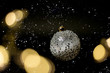 Christmas silver ball with stars and bokeh blurred sparkles and snow on black background.