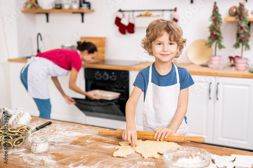 Happy cute boy in apron helping his mom make cookies on xmas eve Canvas Print