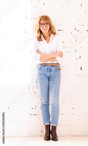 Obraz Full length shot of happy middle aged woman posing at white wall - fototapety do salonu