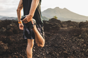 Runner stretching leg and feet and preparing for trail running outdoors. Active and healthy lifestyle concept. Mountain view on background.