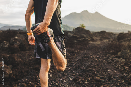 Runner stretching leg and feet and preparing for trail running outdoors Fototapete