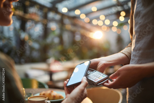 Fototapety, obrazy: Closeup of young woman paying via NFC in cafe, focus on female hands holding smartphone with blank screen to banking terminal, copy space