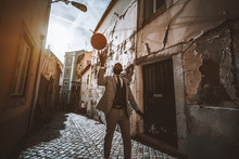 A Fancy African Man In An Elegant Formal Suit With A Necktie Is Spinning A Basketball Above Him While Standing On An Antique Narrow Residential Street With Flaked Walls In Lisbon, Portugal