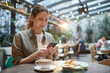 canvas print picture - Portrait of beautiful young woman using smartphone while enjoying evening on outdoor terrace in cafe or coffee shop, copy space