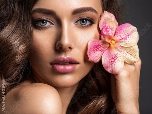 Fototapeta  Stunning girl holds flower near eyes