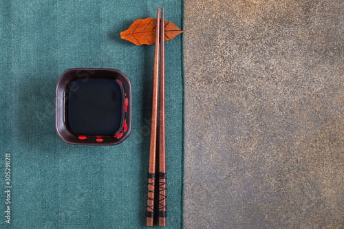 Photo Japanese style soy sauce and chopsticks on stone background with copy space, top