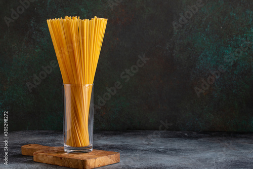 Canvastavla Raw spaghetti bavette in glass on dark background with copy space