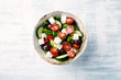 Salad with Kalamata Olives, Cucumber Cherry Tomatoes and Feta Cheese on bright wooden Background. Healthy Snack Idea. Top view. Copy space.