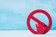 Red Forbidden Sign And Hand  On Blue Background.