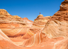 Man Standing High Above The Wave Formation On Sandstone Tower Of Orange And Pink Rock.