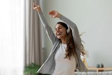 Woman Wearing Headphones Dancing In Living Room At Home