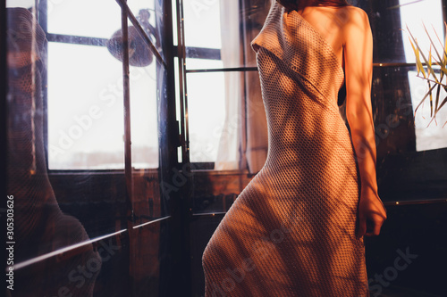 Back view of beautiful young woman taking off a bathrobe, standing with bare back in the bathroom.