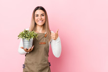 Young Gardener Woman Holding A Plant Smiling And Raising Thumb Up