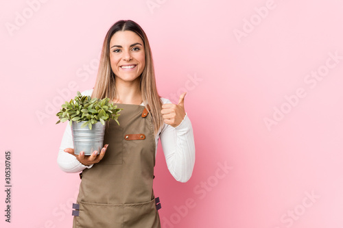Fotografia Young gardener woman holding a plant smiling and raising thumb up