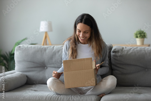 Obraz Overjoyed young woman opens box parcel feels satisfied - fototapety do salonu