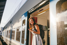 Woman Peeking Out Train. Woman Railway Station. Young Happy Woman Pulling Face Out Train Door Looking For Somebody Railway Station. Travelling. Portrait Girl Standing On Train Door When Arrived
