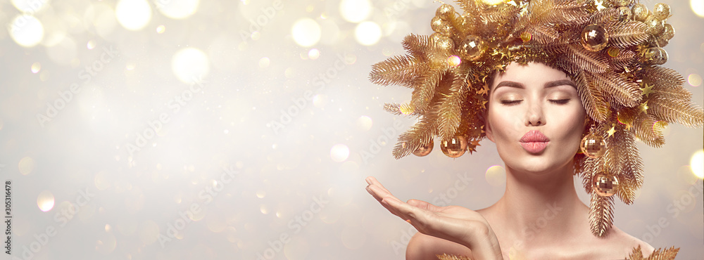 Obraz Christmas Woman with golden spruce tree wreath hairstyle on blurred pastel background. Beautiful Xmas model girl presenting hand, showing product, kiss. Hair style decorated, baubles. Christmas wishes fototapeta, plakat