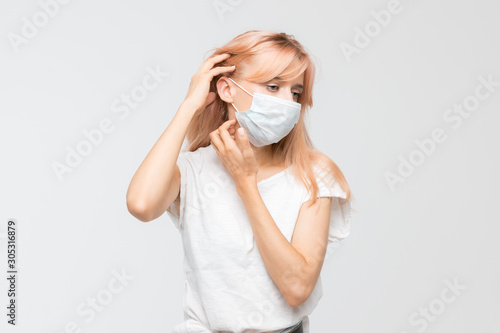 Cropped studio portrait of woman in white t-shirt with medical mask who scratching itchy throat Billede på lærred