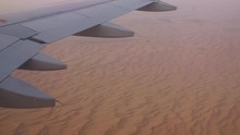 Aerial View Out Of An Etihad Airways Airbus A320-200s Right Window On Final Approach On Abu Dhabi International Airport With The Red Sand Dunes In The Background While Sunset.