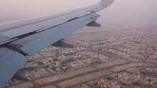 Aerial View Out Of An Etihad Airways Airbus A320-200s Right Window On Final Approach On Abu Dhabi International Airport With The Suburbs In The Background While Sunset.