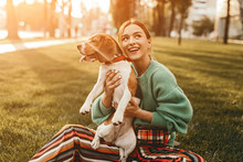 Joyful Woman On Grass Holding Dog Tight And Looking Up