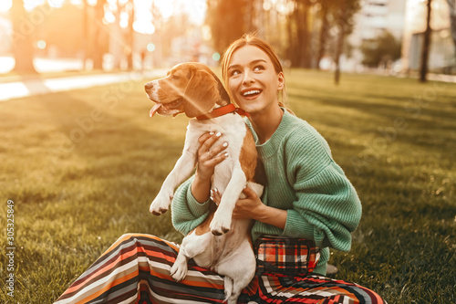 Photographie Joyful woman on grass holding dog tight and looking up