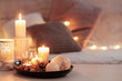 canvas print picture - Christmas decoration   with burning candles on  white table against the background of  sofa with plaids and pillows. Cozy home and holiday concept