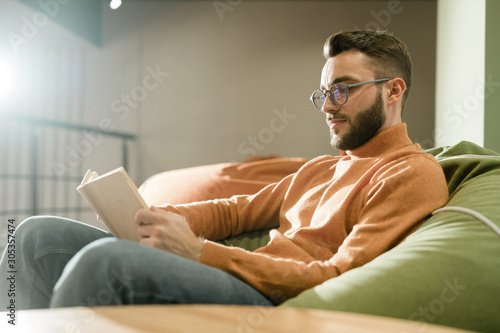 Fototapeta Young relaxed man in casualwear and eyeglasses reading book on comfortable sofa obraz na płótnie