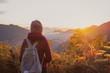 Leinwandbild Motiv Young woman traveler looking at sunset over the mountain