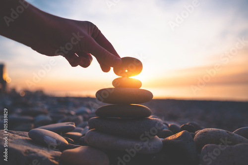 Stone with a hole at sunset. Find a talisman and make a wish - 305359829
