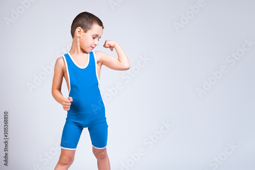 Fotografía Portrait of a little cheerful boy in a blue  wrestling tights shows biceps, looks confidently at him and poses on a white isolated background