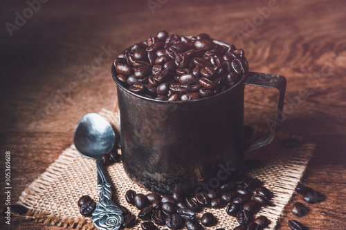 Tuinposter koffiebar Dark roasted coffee beans in a rusty cup on burlap and wood table. Dark mood coffee beans photography.