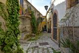 Fototapeta Uliczki - Civitanova del Sannio, 11/23/2019. A narrow street among the old houses of a mountain village in the Molise region