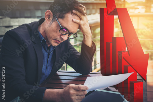 Fototapeta Bad investment or economic crisis concept. Senior businessman is disappointed by business results graph down visual graphic. obraz